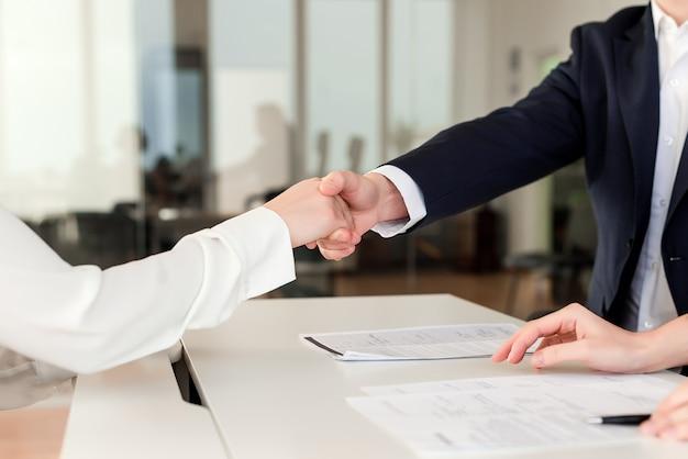 Partner, die hände schütteln und an einem abkommen im büro zusammenarbeiten