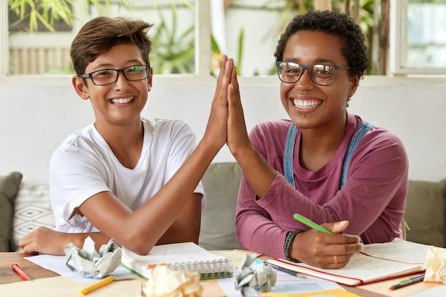 Partnerschafts- und kollaborationskonzept. lächelnde fröhliche junge frauen gemischter rassen geben high five, schreiben notizen in notizbuch, haben fröhliche ausdrücke