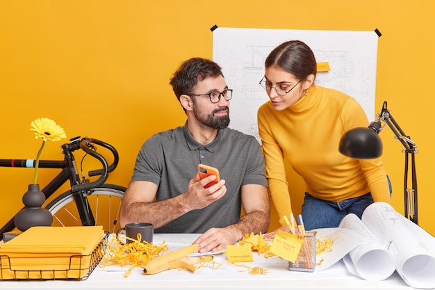Partnerschafts- und kommunikationskonzept. erfahrene büroangestellte von frauen und männern arbeiten an der gestaltung einer grafischen pose auf einem unordentlichen desktop mit blaupausen und generieren kreative ideen für zukünftige architekturprojekte