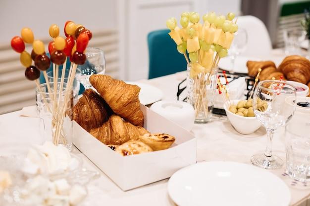 Party-catering. festliches abendessen mit kanapees, croissants, verschiedenen snacks zum feiern von veranstaltungen. foto in hoher qualität