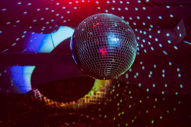 Party-disco-spiegelkugel, die lila lichter reflektiert.