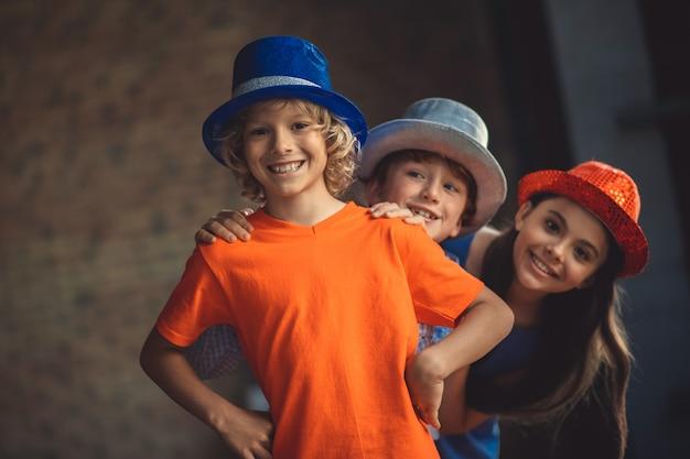 Party. drei freunde in partyhüten sehen fröhlich aus