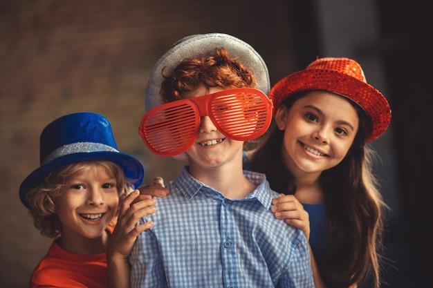 Party. drei kinder in partyhüten fühlen sich glücklich und genossen