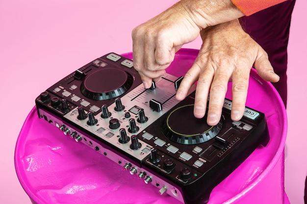 Party fahren. schließen sie herauf älterer mann, der dj-satz lokalisiert auf rosa studiohintergrund spielt. tech und fröhlicher älterer lebensstil, musik, festivalkonzept. trendige farben, ewig jugend. copyspace für ihre anzeige.