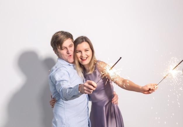 Party-, familien- und urlaubskonzept - junges paar auf der suche nach wunderkerzen auf weißem hintergrund.