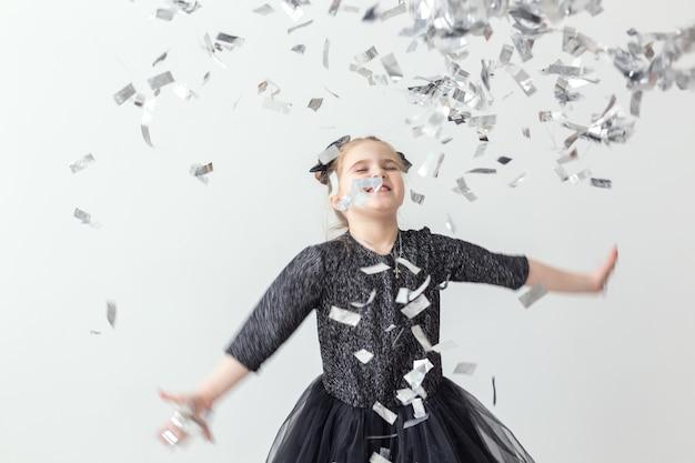 Party, feiertage, neujahr und feierkonzept - weibliches kind, das konfetti wirft.
