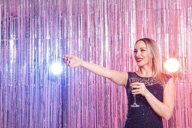 Party-, getränke-, feiertags- und feierkonzept - lächelnde frau im abendkleid mit glas von