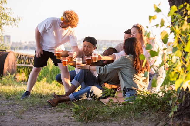 Party gruppe von freunden, die beim picknick am strand bei sonnenschein mit biergläsern klirren