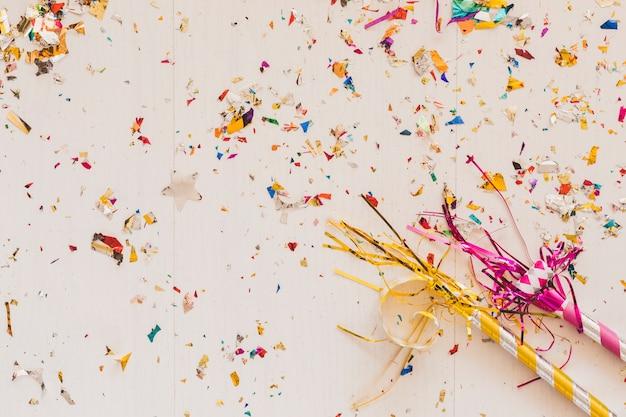 Party hörner auf tisch in konfetti