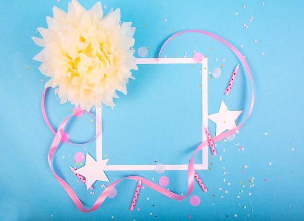 Party holiday oberfläche mit band, sternen, geburtstagskerzen, geschenkbox leerem rahmen und konfetti auf blauer oberfläche
