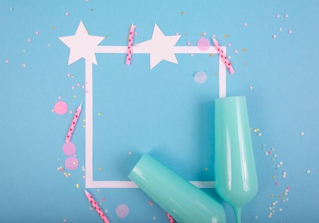 Party holiday oberfläche mit band, sternen, geburtstagskerzen, leerem rahmen und konfetti auf blauer oberfläche