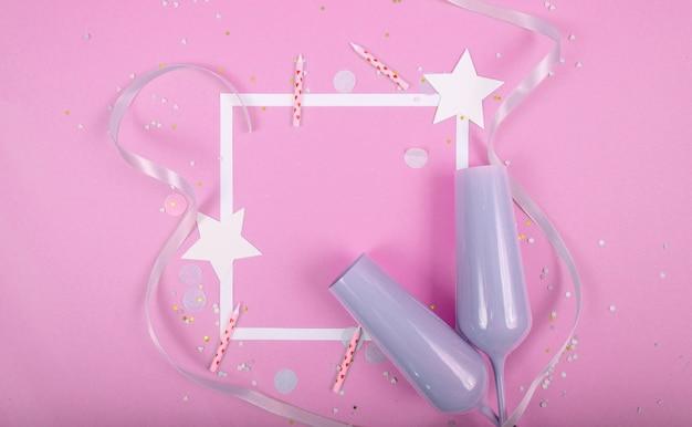 Party holiday oberfläche mit band, sternen, geburtstagskerzen, leerem rahmen und konfetti auf rosa oberfläche