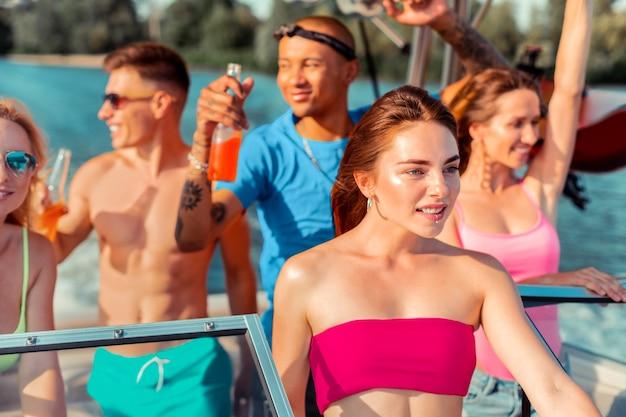 Party im freien. hübsches dunkelhaariges junges mädchen, das in begleitung ihrer feiernden freunde auf einer yacht steht und in die ferne schaut