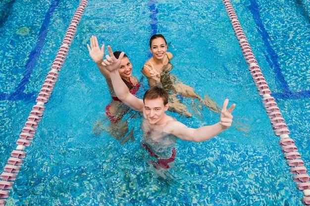 Party im schwimmbad. drei freunde tanzen drinnen