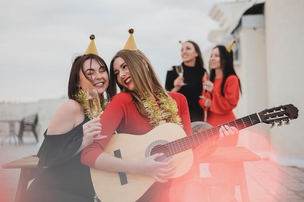 Party machende frauen, welche die gitarre auf der dachspitzenparty spielen