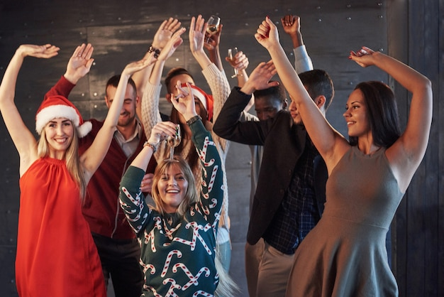 Party mit freunden. sie lieben weihnachten. gruppe nette junge leute, welche die wunderkerzen und sektkelche tanzen in partei des neuen jahres und schauen glücklich tragen. konzepte über zusammengehörigkeitslebensstil