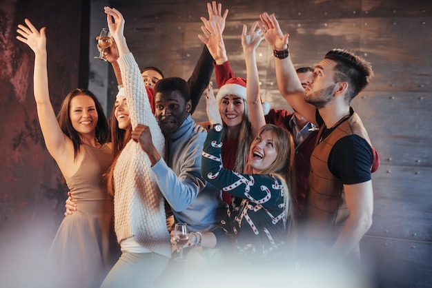 Party mit freunden. sie lieben weihnachten. gruppe nette junge leute, welche die wunderkerzen und sektkelche tanzen in partei des neuen jahres und schauen glücklich tragen. konzepte zum zusammenleben