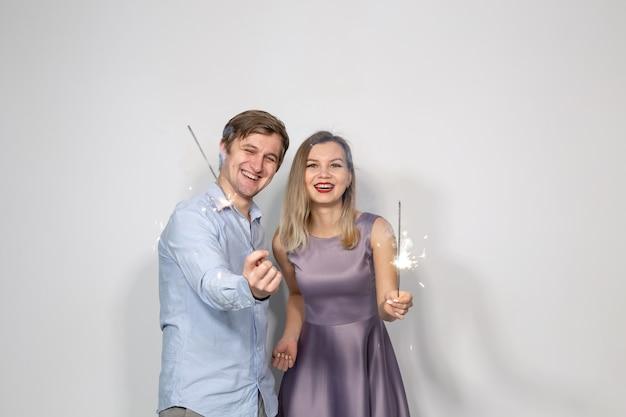 Party-, neujahrs-, weihnachts- und feiertagskonzept - junges paar, das wunderkerzen auf weißem hintergrund hält