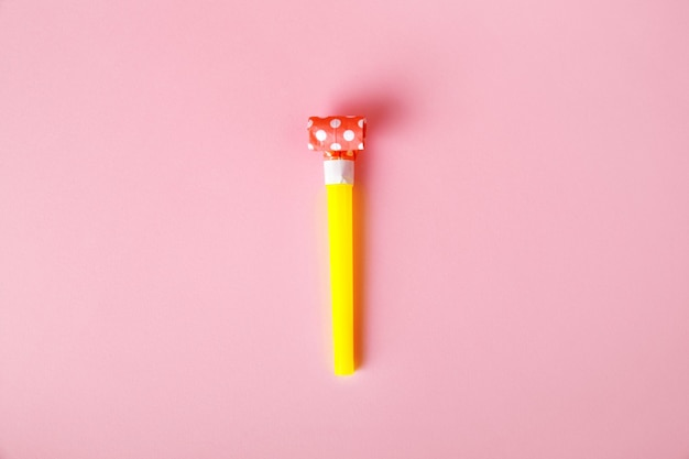 Party pfeife oder gebläse über rosa hintergrund, party- und feierzubehör