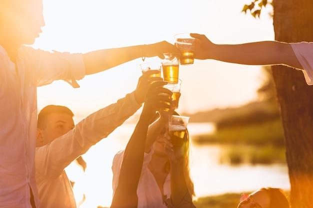 Party schließen sie die hände von freunden, die beim picknick am strand bei sonnenschein mit biergläsern klirren
