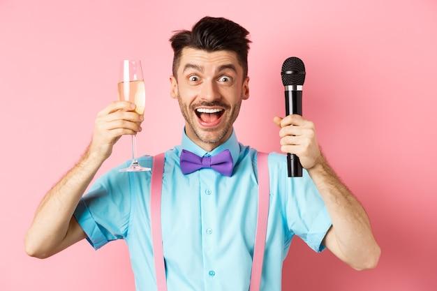 Party- und festveranstaltungskonzept. fröhlicher junger männlicher animateur, der rede im urlaub hält, glas chamapgne erhebt und mikrofon hält, toast auf hochzeit, rosa hintergrund macht.