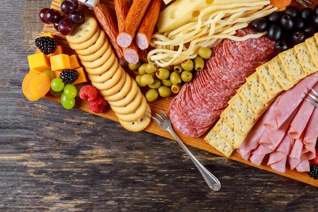 Party-vorspeisenteller bestehend aus käse, crackern, nüssen und anderen party-snacks.