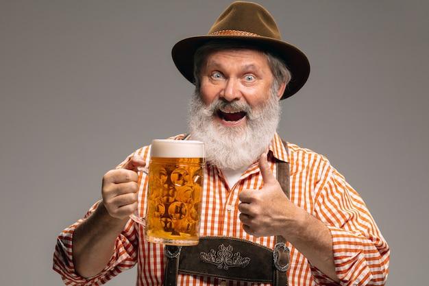 Party zeit. glücklicher älterer mann in traditioneller österreichischer oder bayerischer tracht mit krug bier auf grauem studiohintergrund. exemplar. die feier, oktoberfest, festival, traditionskonzept.
