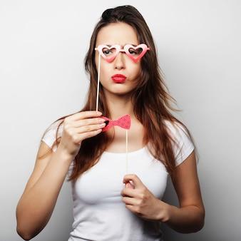 Partybild. verspielte junge frau, die eine partybrille hält. bereit für eine gute zeit.
