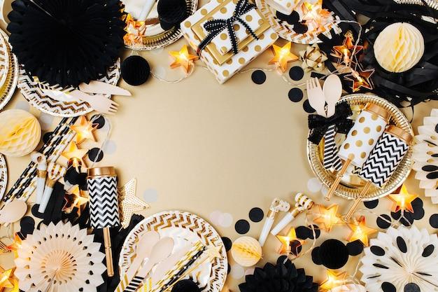 Partydekoration hintergrund. gold und schwarze farbe. flache lage, ansicht von oben