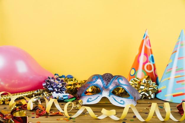 Partydekorationsmaterial mit maskeradekarnevalsfedermaske und -ballonen