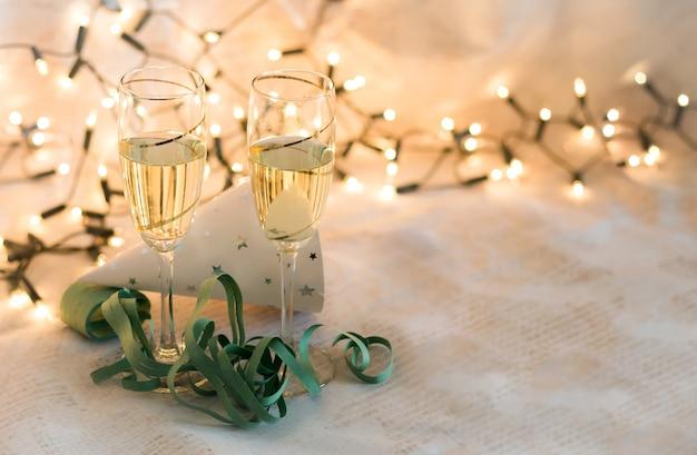 Partyelemente und -gläser des neuen jahres mit champagnerkarte mit dem platz zum schreiben