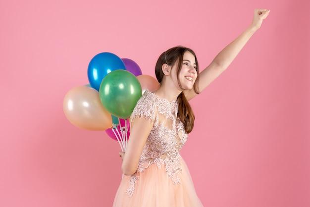 Partygirl hält luftballons hinter ihrem rücken in superheldenpose auf pink
