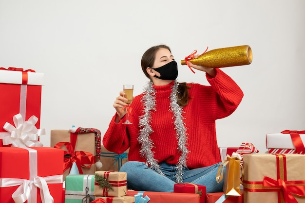 Partygirl mädchen mit schwarzer maske hält champagner, der um geschenke auf weiß sitzt