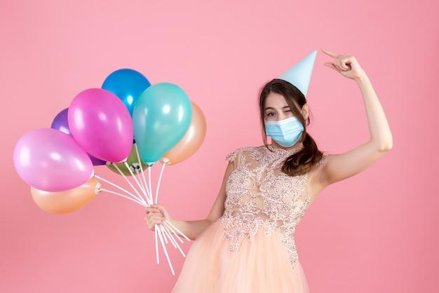 Partygirl mit medizinischer maske, die auf ihre partykappe zeigt, die bunte luftballons auf rosa hält