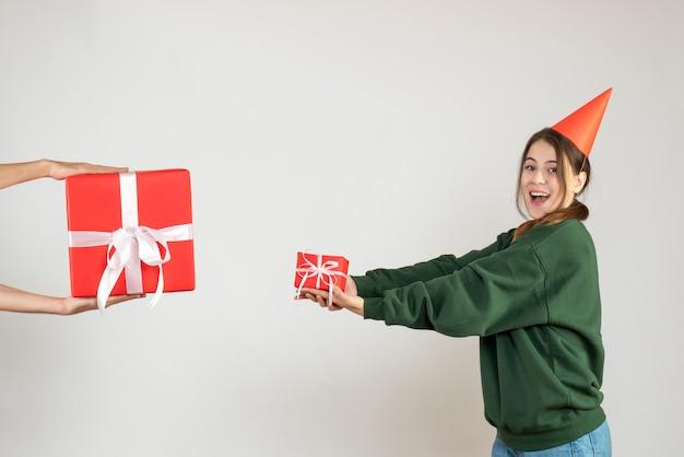 Partygirl mit partykappe, die geschenke auf weiß austauscht