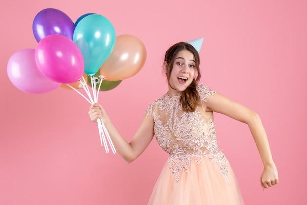 Partygirl mit partykappe, die luftballons hält und auf rosa läuft