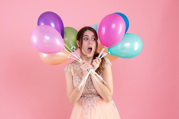 Partygirl mit partykappe, die luftballons nahe gesicht auf rosa hält