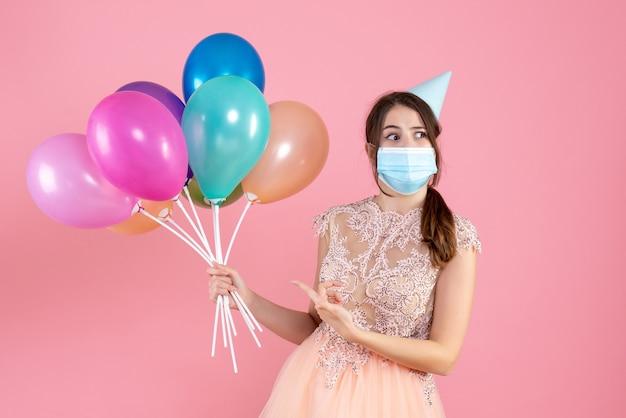 Partygirl mit partykappe, die mit fingerballons auf rosa hält und zeigt