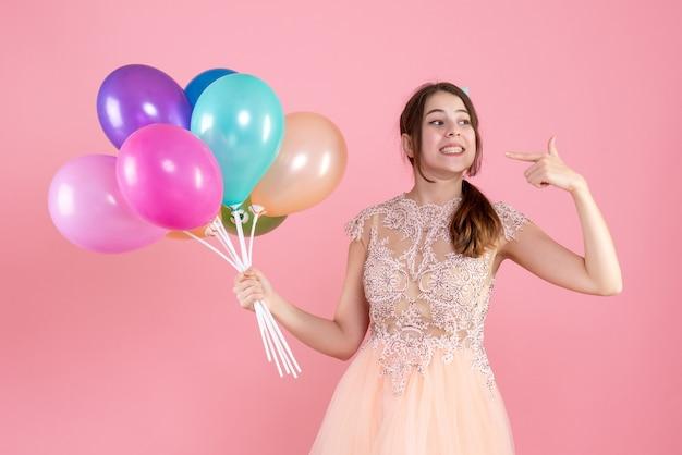 Partygirl mit partykappe hält luftballons, die auf ihr lächeln auf rosa zeigen