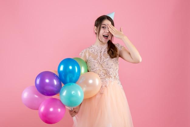 Partygirl mit partykappe hält luftballons, die hand auf ihr auge auf rosa setzen