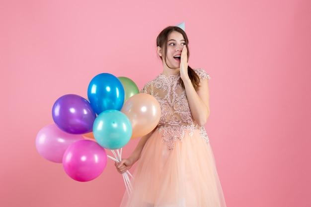 Partygirl mit partykappe hält luftballons, die hand auf ihren mund auf rosa setzen