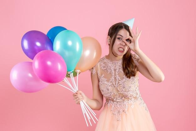 Partygirl mit partykappe hält luftballons, die okey zeichen vor ihrem auge auf rosa putteten
