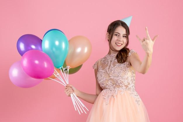 Partygirl mit partykappe hält luftballons, die rockzeichen auf rosa machen