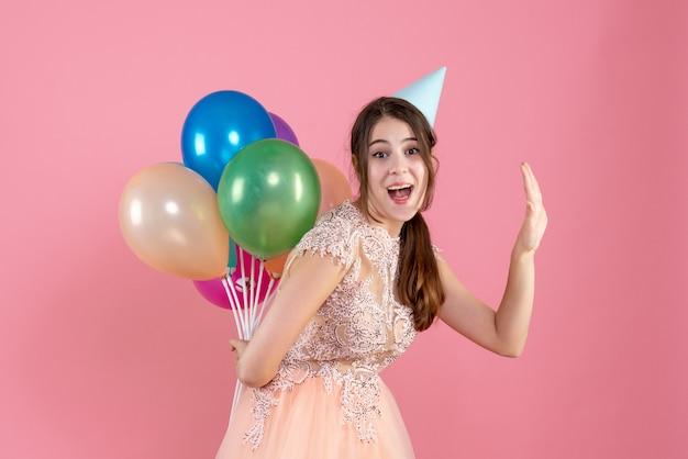 Partygirl mit partykappe hält luftballons hinter ihrem rücken und begrüßt jemanden auf pink