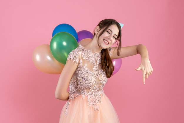 Partygirl mit partykappe hält luftballons hinter ihrem rücken und zeigt auf unten auf pink