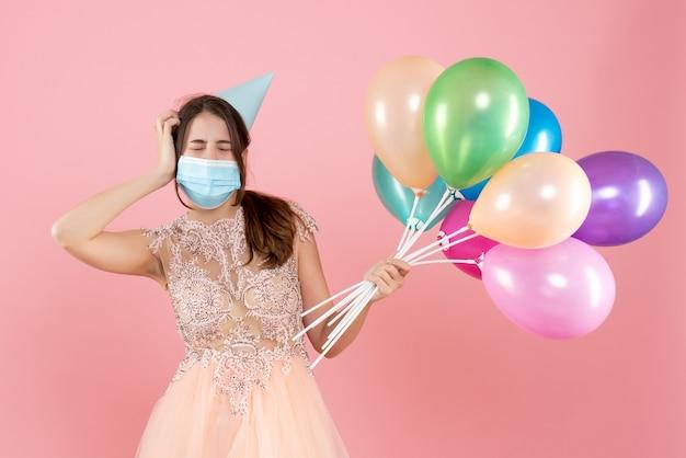 Partygirl mit partykappe und medizinischer maske, die augen schließt, die bunte luftballons auf rosa halten