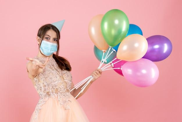 Partygirl mit partykappe und medizinischer maske, die bunte luftballons auf rosa hält