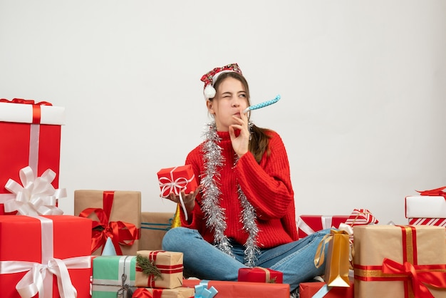 Partygirl mit weihnachtsmütze hält geschenk mit krachmacher, der um geschenke auf weiß sitzt