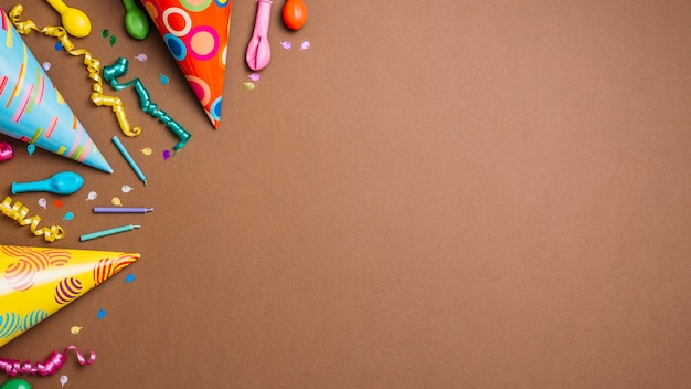 Partyhüte; luftschlangen; kerzen und luftballons mit konfetti auf braunem hintergrund