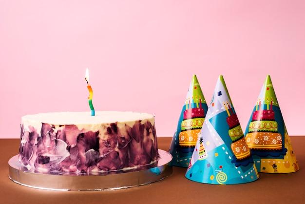 Partyhüte und -kuchen mit brennender kerze auf schreibtisch gegen rosa hintergrund